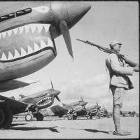 Allies: A Chinese soldier guards American P-40 planes, painted with the shark-face emblem of the 'Flying Tigers,' in China in July 1942. | NATIONAL ARCHIVES AND RECORDS ADMINISTRATION
