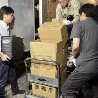 Investigators remove boxes of documents from an apartment in Tokyo's Itabashi Ward last year. Four men were arrested under anti-child-pornography laws in connection to the documents. | KYODO