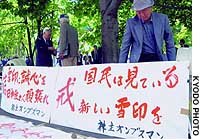 Shareholders of Snow Brand Milk Products Co. brandish a flag of admonishment featuring the appropriate kanji character, 'kai,' near the site of a shareholders' meeting in Sapporo's Chuo Ward.