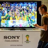 Tuned in: A man walks past a Sony TV set in the Sony Corp. Tokyo headquarters showroom Thursday. The firm said the same day it had swung back to a net profit of $35 mililon for the April-June quarter. | AFP-JIJI