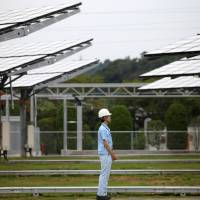 Time and energy: An employee stands in front of concentrator photovoltaic units at Sumitomo Electric Industries Ltd.'s new power plant in Yokohama in July 2012, when the firm demonstrated its megawatt-class power generation/storage system. | BLOOMBERG