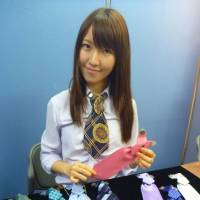 Tied for success: Aya Ohzeki, president and chief executive officer of Noble Apex Inc., shows a range of ties produced by her company in Tokyo in May. | KYODO