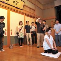 Storyteller for a day: A 'traveler' taking part in a 'rakugo' job experience program sits on the stage at Asakusa Engei Hall in Tokyo on Aug. 3. | YOSHIAKI MIURA