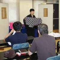 Rakugo storyteller Katsura Udanji explains how to use a washcloth as a stage prop at a hall in Ueno in Tokyo the same day. | MASAAKI KAMEDA