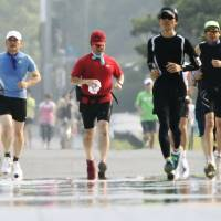 Running to a standstill: Joggers make their way around the Imperial Palace in central Tokyo earlier this month.   KYODO
