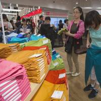Sizing them up: Customers shop for pants at the opening of Fast Retailing Co.'s Uniqlo Lee Theatre flagship store in Hong Kong on April 26. Uniqlo said it will open its biggest flagship anywhere in Shanghai on Sept. 30. | BLOOMBERG