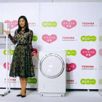 Get smart: Actress Yuki Amami shows off Toshiba Corp.'s new home appliance products compatible with smartphones Thursday in Chiyoda Ward, Tokyo. | KYODO