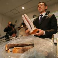 Exhibit A: Junichi Sato shows reporters in Tokyo on May 15, 2008, the whale meat that was in a box he took from Seino Transportation Co.'s Aomori branch. | GREENPEACE JAPAN
