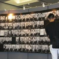 Learning lessons: A visitor looks at portraits of dead victims of Minamata disease at an exhibition designed to raise awareness of the mercury-poisoning disease, at Meiji University in Tokyo on Saturday. | KYODO PHOTO