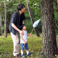 Summer fun: Prince Hisahito catches insects with Prince Akishino at the Imperial Villa in Tochigi Prefecture on Aug. 18. | KYODO PHOTO