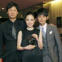 Head and shoulders above: Eri Fukatsu on Monday holds her best actress award, which she won for her performance in 'Akunin' ('Villain'), at the 2010 Montreal World Film Festival. She is flanked by the film's director, Lee Sang Il (left), and Satoshi Tsumabuki, who played the villain. | KYODO PHOTO