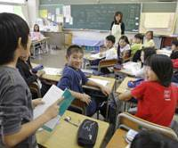 School zone: A fifth-grader answers a question while another student (below) takes notes during a math class with teacher Kazuyo Arai at Honmoku Elementary School in Yokohama in May. | AP PHOTO