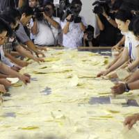 Ballots are tallied for the Nago municipal assembly election Sunday. According to the results, a majority of assembly seats went to candidates who support Mayor Susumu Inamine's opposition of the relocation of a U.S. Marine base in the Okinawan city. | KYODO PHOTO
