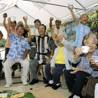 The winning side: Three successful antibase candidates (from left in front row) in the municipal assembly election in Nago, Okinawa Prefecture, raise a toast with residents Monday in the city's Henoko area. | KYODO PHOTO