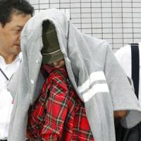 Under cover: Tomoya Ikeda, one of two men arrested Monday over an investment scheme, is escorted by an investigator to a police station in Ichinomiya, Aichi Prefecture.   KYODO PHOTO