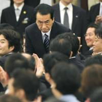 Standup guy: Prime Minister Naoto Kan rises at a Tokyo hotel after being re-elected president of the Democratic Party of Japan on Tuesday. | KYODO PHOTO