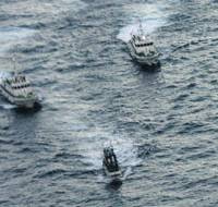 Outnumbered: A Taiwanese protest vessel (center) is monitored by Japan Coast Guard patrol craft Tuesday morning off the Senkaku Islands in the East China Sea.   KYODO PHOTO/JAPAN COAST GUARD