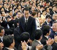 New era begins: A stern-faced Prime Minister Naoto Kan bows to party members after being re-elected president of the Democratic Party of Japan in Tokyo on Tuesday. Below: Kan and rival Ichiro Ozawa bow to each other afterward.   KYODO PHOTO, SATOKO KAWASAKI PHOTO