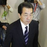 Hallowed halls: Prime Minister Naoto Kan walks through the Democratic Party of Japan's party headquarters in Tokyo on Wednesday. | KYODO PHOTO