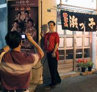 A bite out of tourism: A Chinese tourist poses outside an 'izakaya' restaurant in Hokkaido in June. People in the tourism industry fear that strained Japan-China ties could hurt business. | KYODO PHOTO