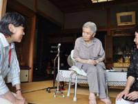 Alive and well: A municipal official talks with 100-year-old Mitsue Watase at her home in Kobe on Aug. 10 as officials began a special program to confirm the whereabouts of centenarians. | KYODO PHOTO