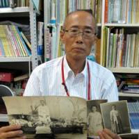 Picture show: Kim Sin Yong holds photos of ethnic Korean residents of Japan for a planned exhibition in Kobe. | KYODO PHOTO