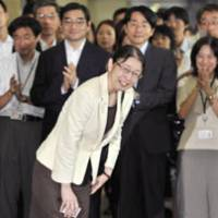 Back to work: Health ministry official Atsuko Muraki smiles Wednesday as her colleagues welcome her at the entrance to the Health, Labor and Welfare Ministry following her acquittal in a postal abuse case. | KYODO PHOTO