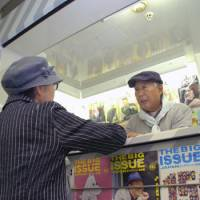 Finding a home: A homeless man hawks The Big Issue magazines in a shop in the Nishi-Umeda subway station in Osaka on Friday. | KYODO PHOTO