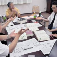 Signing on: Members of the Japan Institute for Sign Language Studies discuss revisions to the Japanese Sign Language Dictionary during a meeting in Kyoto in June. | KYODO PHOTO