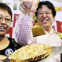 Worth its weight in gold: A man points to a Mido-Suji 'okonomiyaki' pancake with a pure gold 'teko' spatula in Kita Ward, Osaka, on Oct. 6. The pancake was the winning recipe in Yukari's Teko-1GP contest seven years ago. | KYODO PHOTO