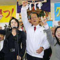Victorious: Liberal Democratic Party lawmaker Nobutaka Machimura (center) and his supporters celebrate his victory in the Lower House by-election for the Hokkaido No. 5 constituency on Sunday. | KYODO PHOTO
