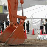 Big scoop: Japan Nuclear Fuel Ltd. employees watch the start of construction of a plant to produce plutonium-uranium mixed oxide, or MOX, fuel, in Rokkasho, Aomori Prefecture, Thursday. | KYODO PHOTO
