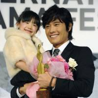 Megastar: South Korean actor Lee Byung Hun holds Japanese child actress Mana Ashida after receiving the Best Actor in Asia award Monday in Tokyo. | KYODO PHOTO