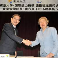 Teaming up: Sadako Ogata, president of the Japan International Cooperation Agency and former U.N. High Commissioner for Refugees, and University of Tokyo President Junichi Hamada participate in a signing ceremony at the university on Oct. 18. | YOSHIAKI MIURA PHOTO