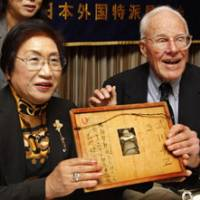 Long time coming: Franklin Hobbs, a former U.S. soldier who fought in the Battle of Iwojima, and Chie Takekawa, whose father was killed on the island, hold a framed letter and a photo of her sister at the Foreign Correspondents' Club of Japan in Tokyo on Friday.   AP PHOTO