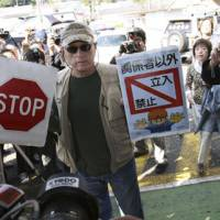 Keeping active: Ric O'Barry, whose efforts to save dolphins are documented in the Oscar-winning film 'The Cove,' holds up signs Tuesday saying 'Stop' and 'Keep out except persons concerned' outside the community center in Taiji, Wakayama Prefecture. | AP PHOTO
