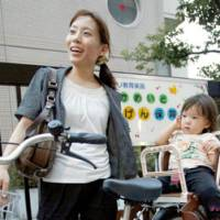 Stick or twist?: Ayako Morikawa picks up her daughter after work from a nursery school in Koto Ward, Tokyo, in September. | KYODO PHOTOS