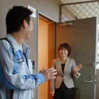 Miho Minaka sees off her husband at their home in Nisshin, Aichi Prefecture, before leaving for work in neighboring Gifu Prefecture in September.