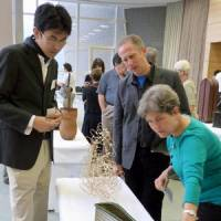Master craftsman: Hajime Nakatomi (left) explains his work to art collectors from the United States at an exhibition of bamboo crafts at the Beppu International Convention Center in Oita Prefecture last month. | KYODO PHOTO