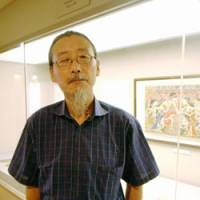 Preservationist: Isamu Sakamoto, an expert on restoring old documents, poses in front of a painting used in an ancient Indonesian performance art at a museum in Tokyo on July 1. | KYODO PHOTO