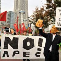 No disguising the message: A man wearing a Barack Obama rubber mask holds up a mask of Prime Minister Naoto Kan at an anti-APEC rally in Yokohama on Saturday. | YOSHIAKI MIURA PHOTO