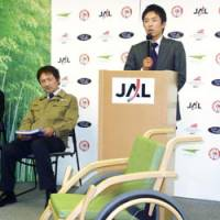 Wood to go: Baseball commentator Norihiro Akahoshi, who was once on the verge of requiring a wheelchair due to an injury, shows off Japan Airlines Corp.'s bamboo wheelchair at Tokyo's Haneda airport.   KYODO PHOTO