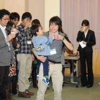 Information gathering: Soichiro Nishimura (holding a child), who is a representative of Fathering Japan Student's, and others socialize during a meeting about child-rearing in Tokyo on Dec. 16. | SATOKO KAWASAKI PHOTO