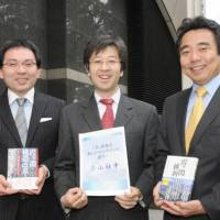 Looking in: Members of Aoyama Shachu (from left) Manabu Kamiya, Ichiro Asahina and Hiromichi Endo show off the books that Project K has published and a brochure of their think tank in Minato Ward, Tokyo, on Dec. 7. | SATOKO KAWASAKI PHOTO