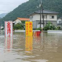 You don't say: A security guard stands near signs warning of street closures due to flooding in the city of  Tottori on  Thursday. Heavy downpours in  Tottori and neighboring prefectures caused widespread flooding and mudslides. | KYODO