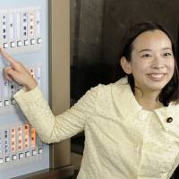 Japanese Communist Party lawmaker Yoshiko Kira presses a button to show her attendance at the Diet. | KYODO