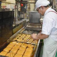 Top item: Kazuhiro Kishida cooks up some deep-fried tofu in the city of Fukui in July. | KYODO