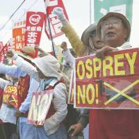 Speaking up: Residents stage a rally Saturday morning at one of the gates for the Futenma airbase in Okinawa Prefecture to protest the arrival of more Osprey aircraft.   KYODO