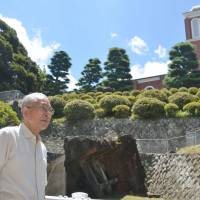 Keeping faith: Catholic Shigemi Fukahori stands in front of the bell tower of the original Urakami Cathedral (center, front) in Nagasaki on July 17. Behind it is the rebuilt Urakami Cathedral.   KYODO