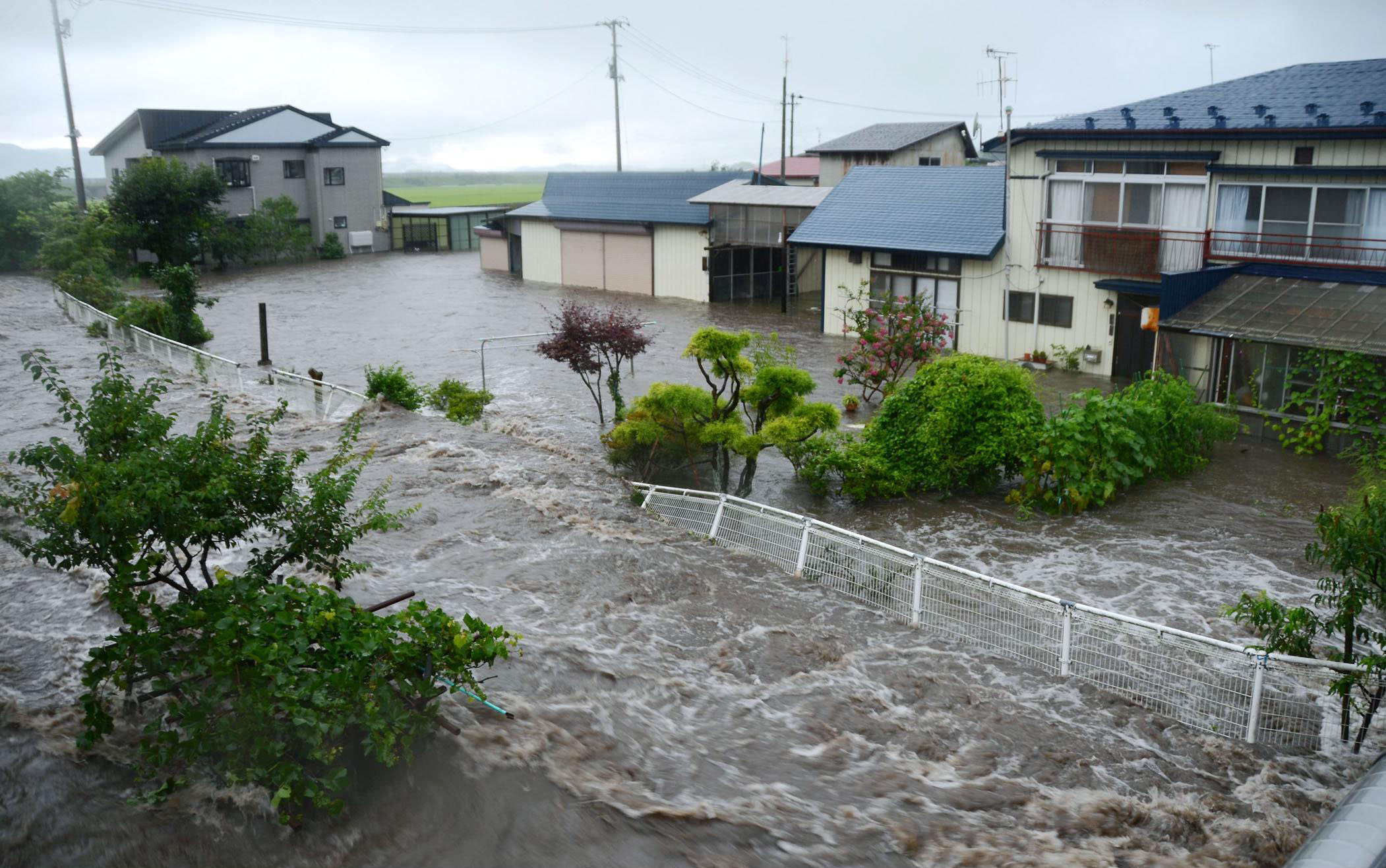 Low blow: Houses in Odate, Akita Prefecture, are flooded amid heavy downpours early Friday. | AKITA SAKIGAKE SHIMPO/KYODO